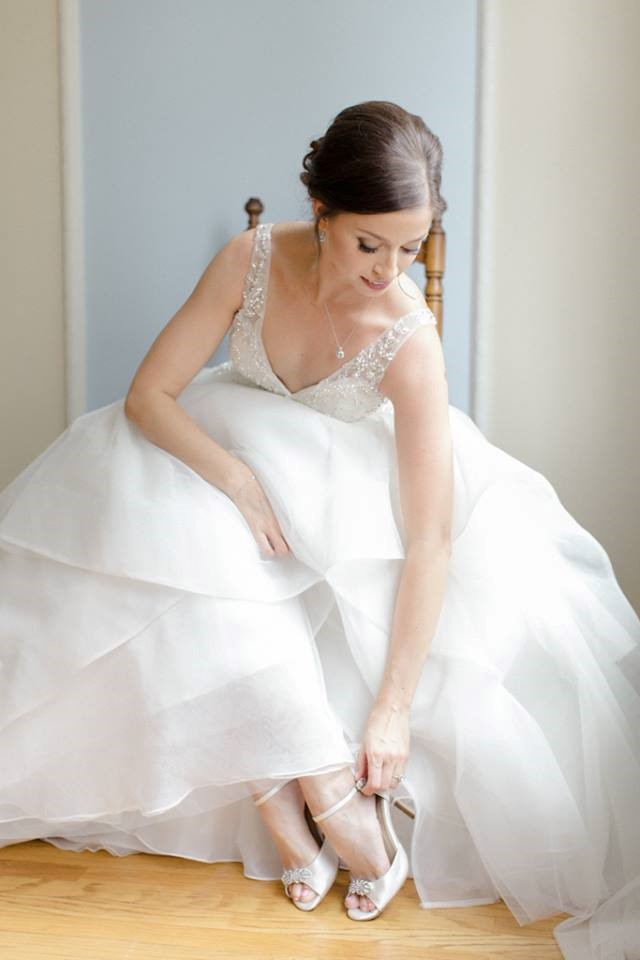 Bride in wedding dress sitting down adjusting her wedding shoes.