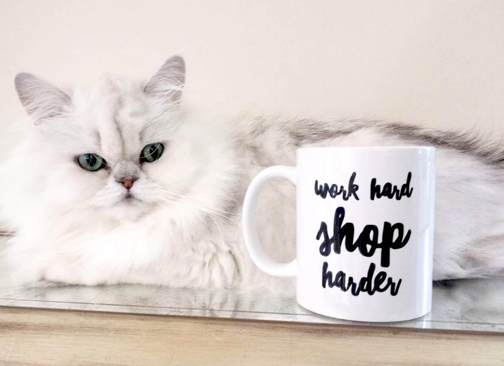 Bentley the cat with coffee mug, work hard shop harder.