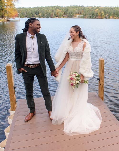 Bride and groom on a dock holding hands and smiling at each other.