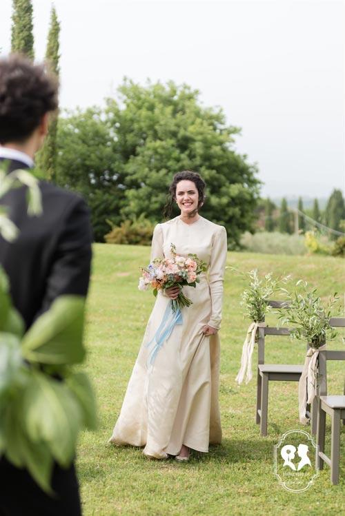 Bride in a field looking at groom