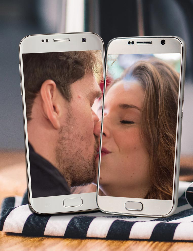 Two cell phones groom on one phone bride in the other together kissing.