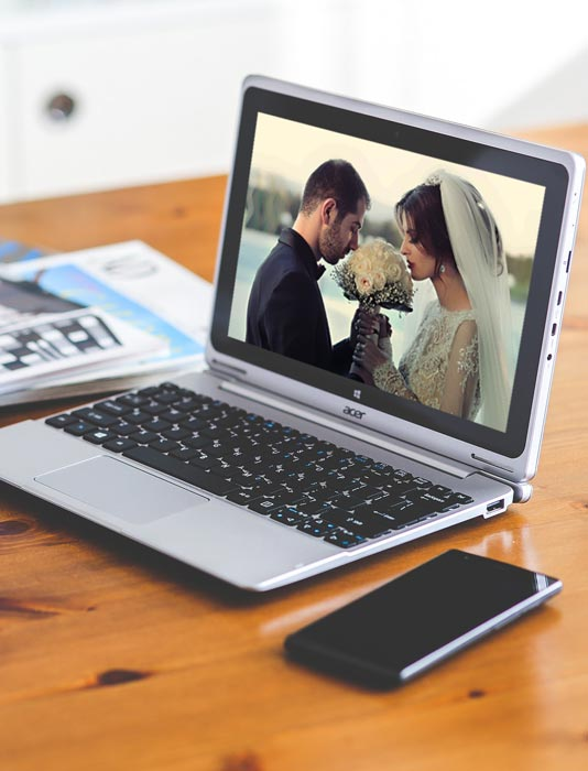 Wood desk with laptop open to scene of bride and groom.