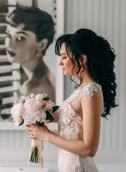 Brunette bride in wedding dress holding the bouquet.