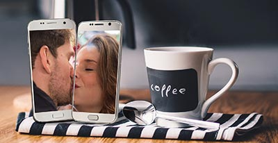Two cell phones aligned to show couple kissing